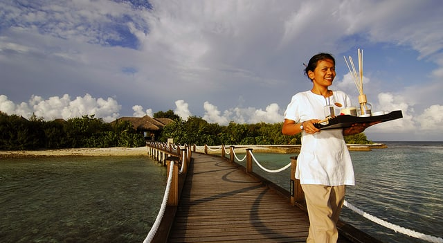 Junge Frau serviert Drinks auf einem Hozsteg über dem Meer, im Hintergrund eine Palmeninsel.