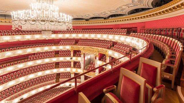 Ein edler Opernsaal mit roten Sitzen und einem grossen Kronleuchter.