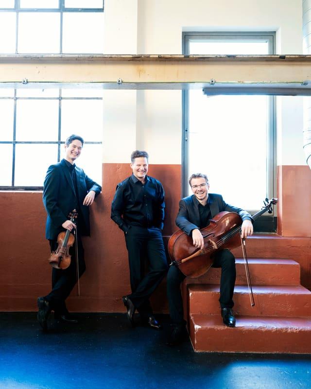 das Oliver Schnyder Trio mit dem Geiger Andreas Janke, dem Cellisten Benjamin Nyffenegger und dem Pianisten Oliver Schnyder. Sie befinden sich an einer Bar im Eingangsbereich der Tonhalle Maag in Zürich. Der Boden ist dunkelblau. Die Wand ist im unteren Teil braun, im oberen Teil weiss gestrichen. Im Hintergrund weisen ein grosses Fenster und ein starker Metallbalken darauf hin, dass die Tonhalle Maag früher als Industriegebäude gedient hat.  Rechts im Bild führt kleine Treppe zu einer Glastür. Fenster und Glastür sind weiss belichtet, draussen scheint die Sonne. Die drei Musiker tragen dunkle Anzüge mit schwarzen Hemden.