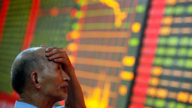 Ein Börsenhändler hält sich den Kopf, dahinter sieht man eine Aktienlinie im Sinkflug.