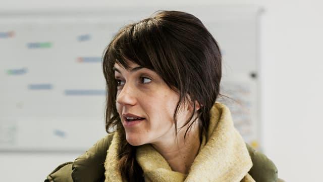 Junge Frau mit dunklen, langen Haaren steht in Winterkleidung in einem Büro.