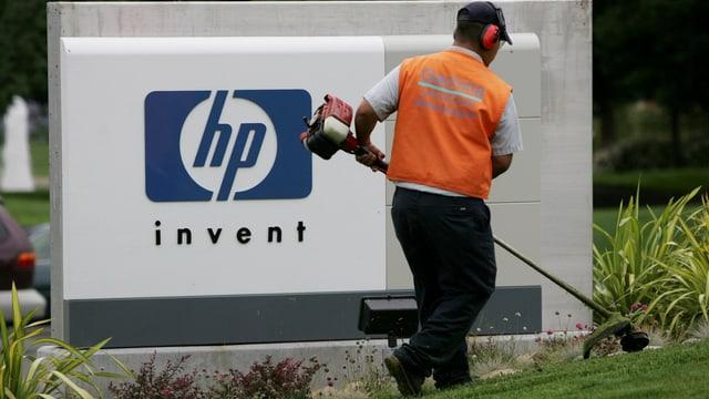 Angestellter mäht vor dem Firmenschild von HP den Rasen