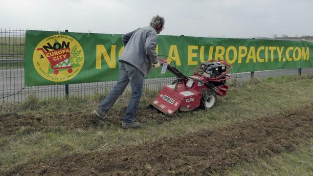 Ein Mann mäht Rasen vor einem Plakat.