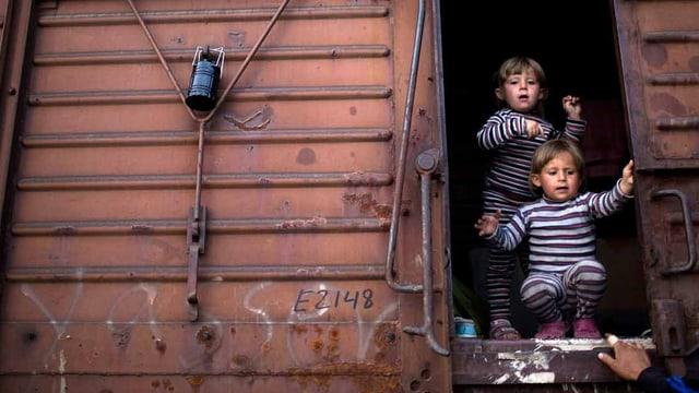 Kinder leben in einem Eisenbahnwaggon.