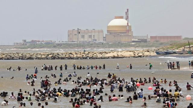 Menschen stehen an einem Strand im Wasser, im Hinterdrund ein AKW mit einer Betonkuppel.