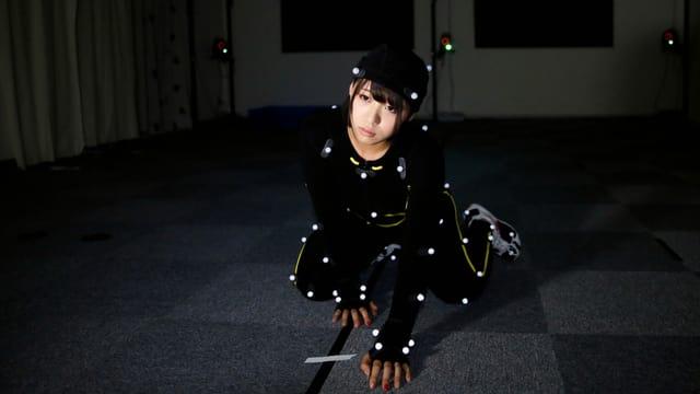 Eine Frau in einem dunklen Raum. Sie trägt einen schwarzen Anzug mit weissen Punkten drauf.