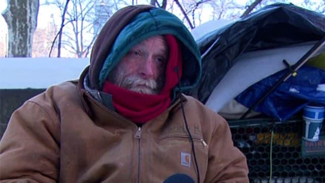 Ein Obdachloser in Mantel und Schal.