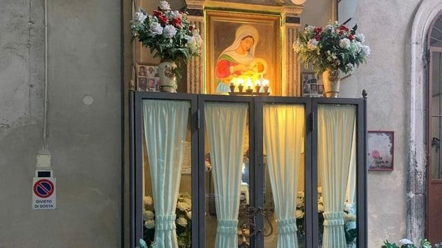 Altar mit Heiligenbild und Fotos