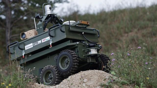 Ein panzerähnliches, dunkelgrünes Fahrzeug mit einem Minikameraaufsatz fährt durch unwegsames Gelände.