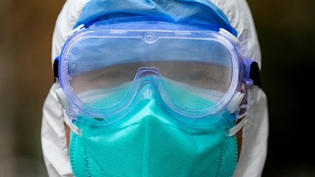 Eine Person mit Schutzmaske und Schutzanzug.