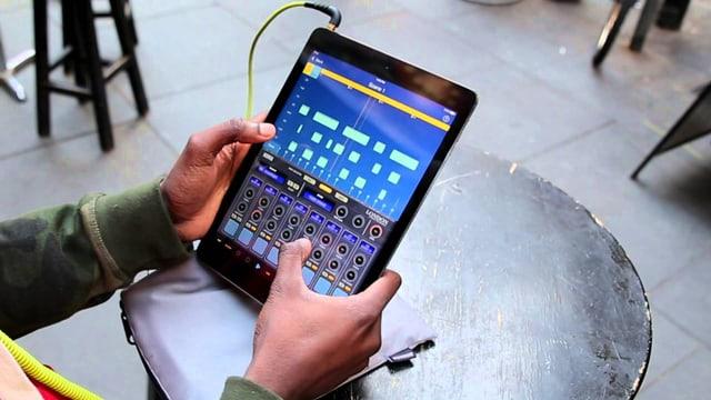 Zwei Hände bedienen ein iPad mit der KORG App