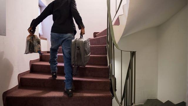 Ein Mann geht mit einem Koffer eine Treppe hoch.