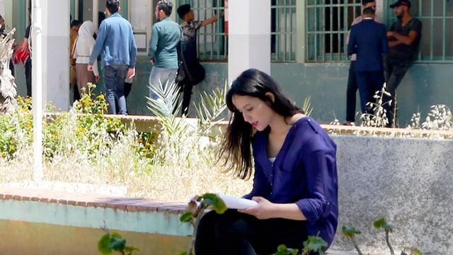 Frau sitzt lesend auf Stufen.