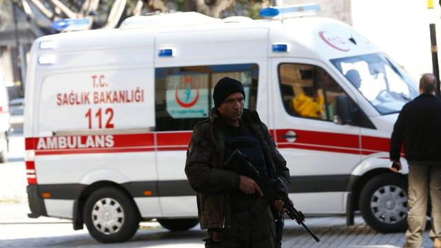 Ein bewaffneter Polizist vor einem Ambulanz-Wagen
