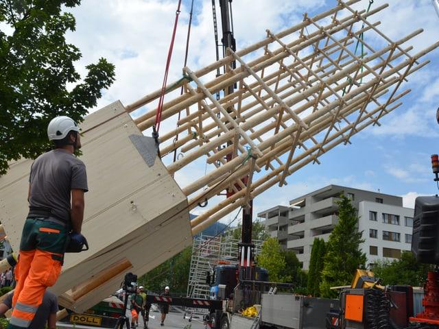 Arbeiter stellen den Holzturm mit einem Kran auf.