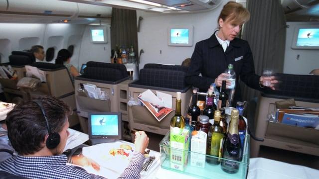 Eine Flight Attendant verteilt an Bord eines Flugzeug Getränke.