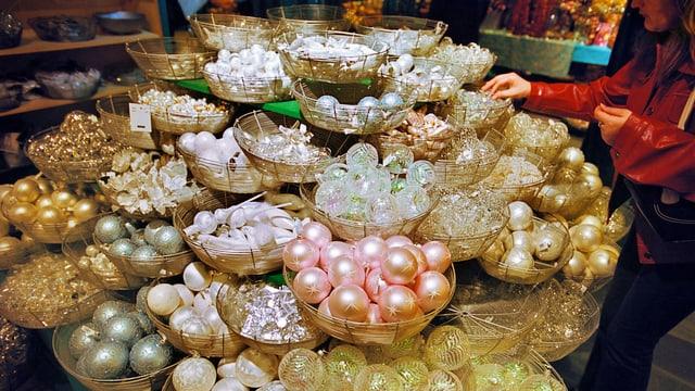 Eine Kundin begutachtet eine grosse und bunte Auswahl an Weihnachtskugeln im Glattzentrum.