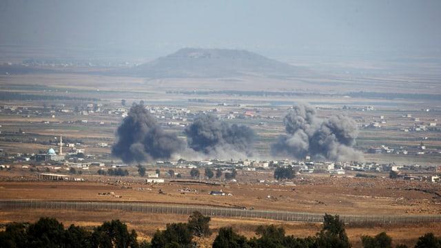 Explosioinswolken in der Ferne, in ländlichem Gebiet mit einigen Häusern.