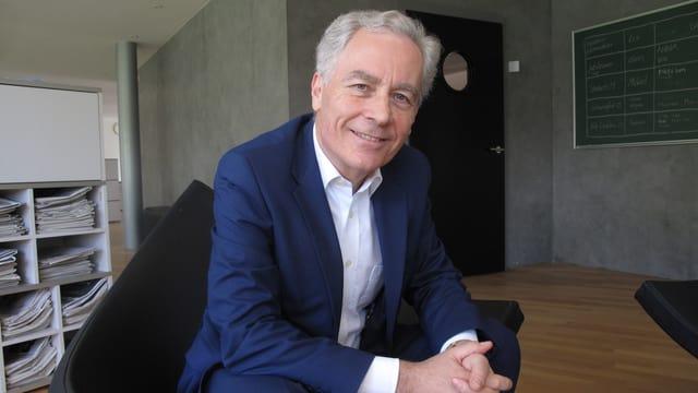Der Rektor der Universität Luzern sitzt auf einem Stuhl.