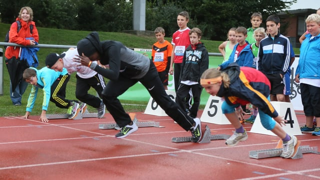 Murielle Ahouré rennt gemeinsam mit Kindern auf der Bahn.