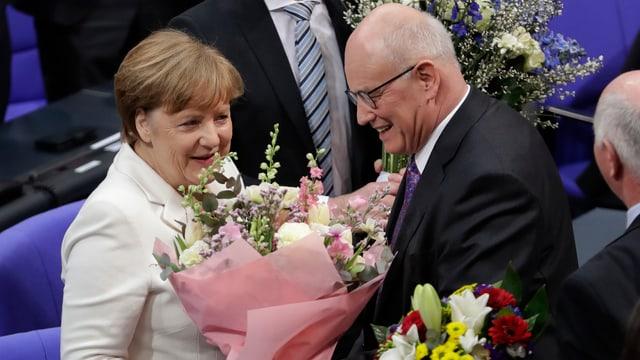 Angela Merkel erhält Blumen von Volker Kauder.