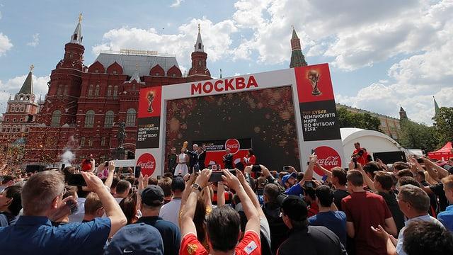 Menschenmenge vor einer Bühne, die vor dem Kreml aufgestellt ist.