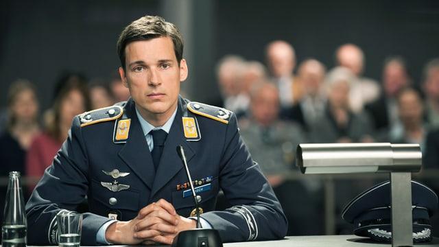 Ein Mann in Pilotenkluft sitzt vor einem Mikrophon.