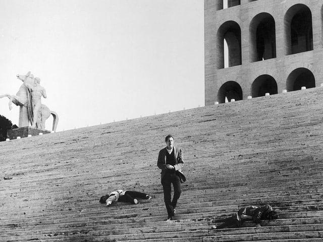 Schwarzweissbild: Ein Mann steht einsam auf einer grossen Trepp, auf der zwei Leichen liegen.