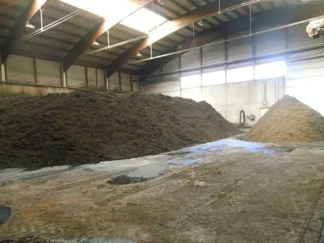 Zwei grosse Komposthaufen in einer Halle mit Oberlicht.