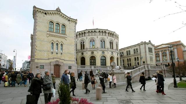 Am Parlamentsgebäude in Oslo gehen Menschen vorbei.