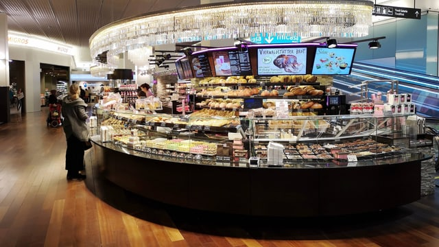 Eine Bäckerei: eine Person steht vor dem Verkaufstresen.