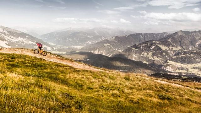Ein Mountainbiker fährt über einen Hügel