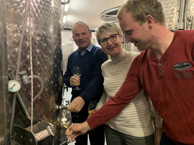 Christian Herzog, Sohn Manuel Herzog und Frau Monika Herzog degustieren Wein im Weinkeller.