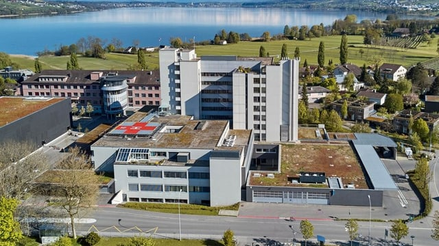 Verschiedene grosse Gebäude (Spital) im Hintergrund ein See.