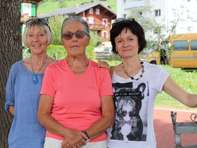 Drei Frauen lächeln in die Kamera.