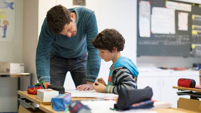 Ein Lehrer hilft einem Schüler bei den Hausaufgaben
