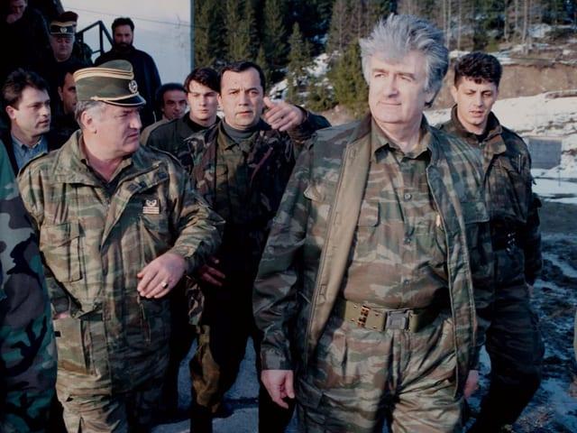 Karadzic und Mladic in Militärkleidung auf einem Landweg.