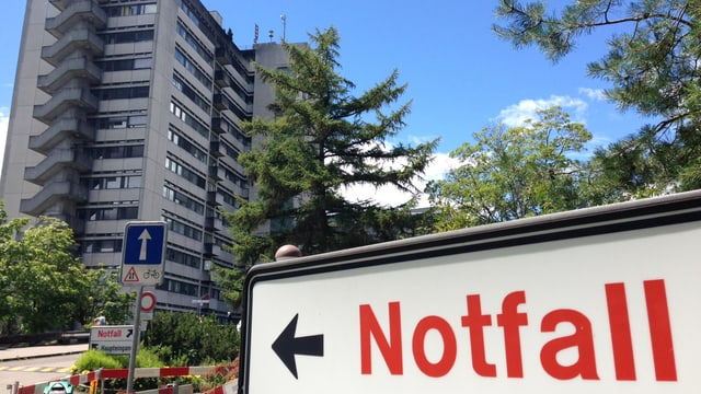Schild mit Aufschrift Notfall neben Spital-Hochhaus