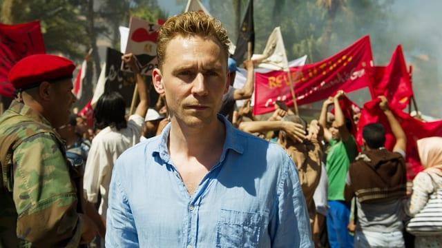 Ein Mann blickt in die Kammera, dahinter hat es viele protestierende Menschen.