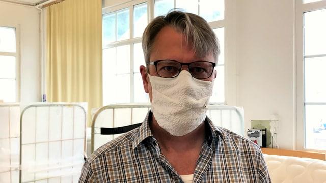 Ein Mann in Hemd und Gesichtsmaske.