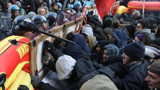 """Politiker halten Studenten zurück, die gegen die neo-faschistische Bewegung """"CasaPound"""" rebelliert."""