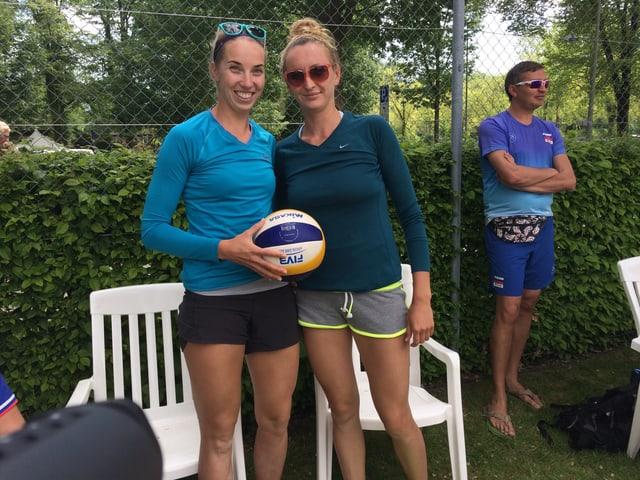 Zwei grosse, blonde Frauen posieren mit einem Volleyball in der Hand.