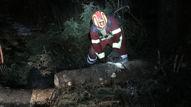 Feuerwehrmann zersägt Baumstamm mit Motorsäge