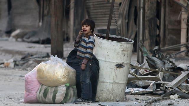 Ein Kind mit Plastiksäcken auf einer Strasse voller Trümmer