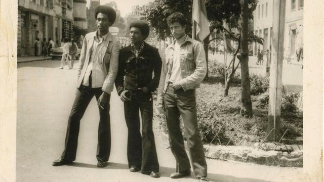 Drei Männer stehen in 70er-Kleidern auf einer Strasse.