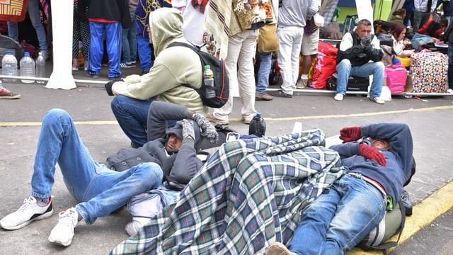 Junge Männer liegen in der Kälte auf dem Boden, zugedeckt von einer Wolldecke. Sie tragen Handschuhe.