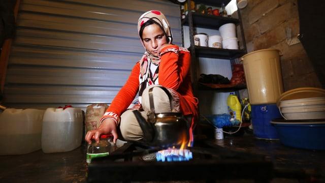 Ein Mädchen mit Kopftuch kocht mit einem Gasbrenner Wasser.