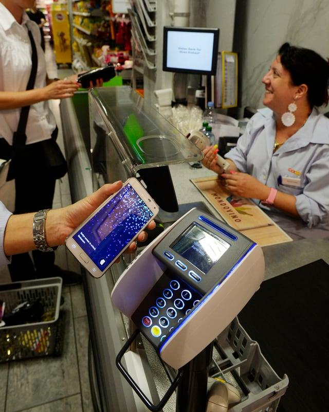Ein Kunde zahlt im Supermarkt an der Kasse mit einer Handy-App.