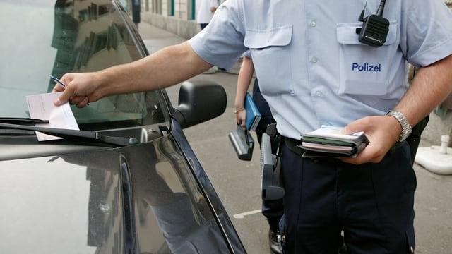 Ein Polizist verteilt eine Parkbusse.