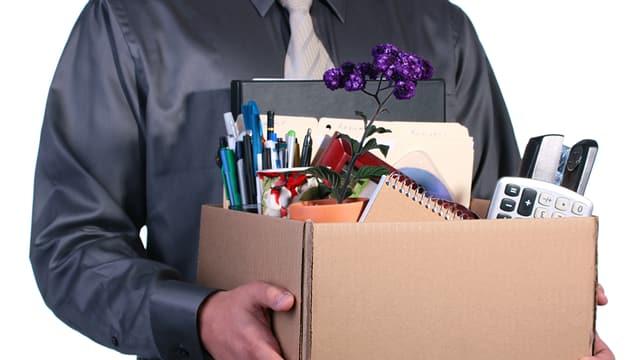 Ein entlassener Mann trägt einen Karton mit seinen persönlichen Effekten aus dem Büro